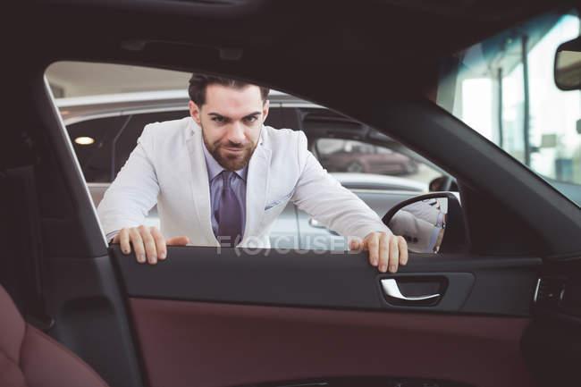 Портрет впевнено продавець, розглядаючи в салоні автомобіля — стокове фото