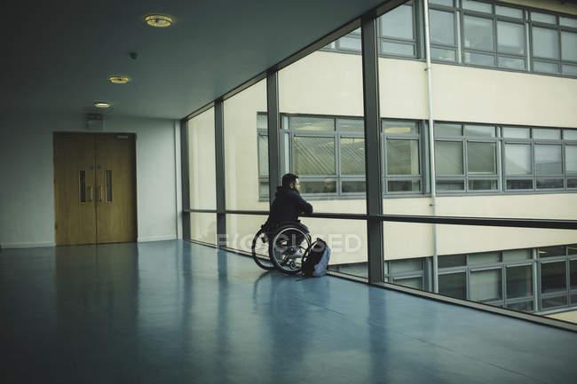 Vista trasera del hombre discapacitado en silla de ruedas mirando desde el cristal - foto de stock