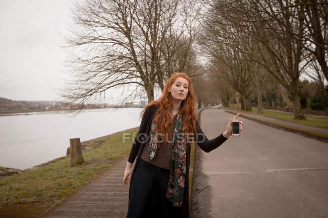 Belle femme auto-stop sur route de campagne — Photo de stock