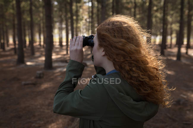 Woman looking through binoculars in forest on a sunny day — Stock Photo