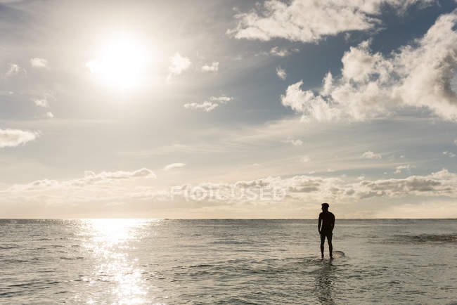 Male surfer surfing with surfboard in the sea at dusk — Stock Photo