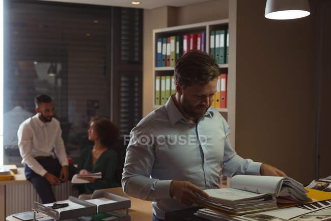 Verificação de documentos de arquivo, enquanto os colegas interagindo em segundo plano no escritório de arquiteto — Fotografia de Stock