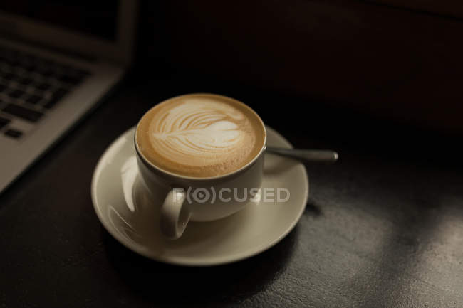 Cup of cappuccino on table in the cafe — Stock Photo
