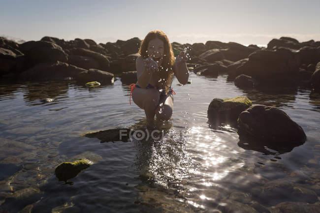 Glückliche Frau im Bikini mit seichtem Wasser spielen — Stockfoto