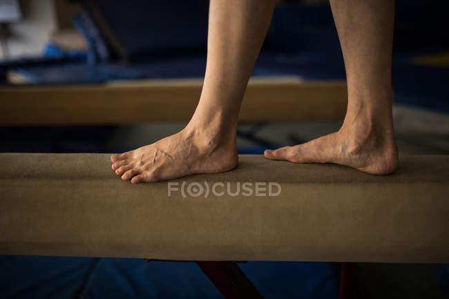 Спортсменка, балансируя на деревянный брусок в фитнес-студии — стоковое фото