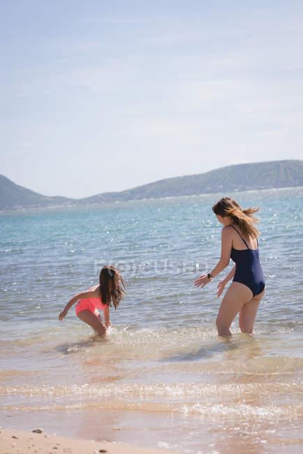 Mãe e filha se divertindo na praia em um dia ensolarado — Fotografia de Stock