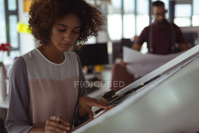 Female architect designing on drafting table in the office — Stock Photo