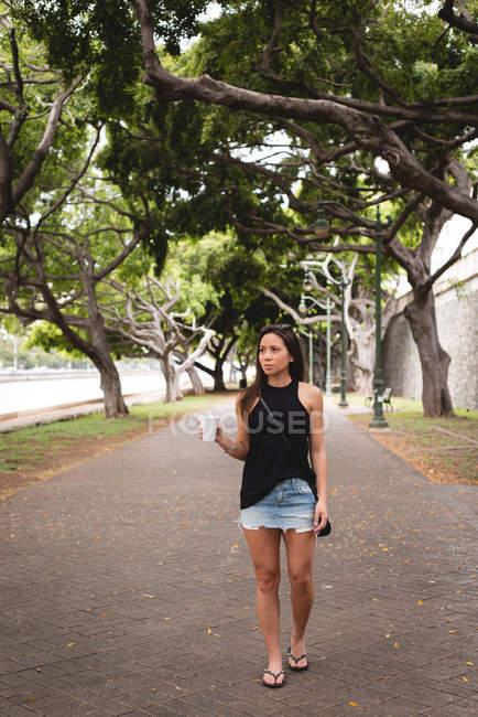 Mujer caminando con café en la acera de la ciudad - foto de stock