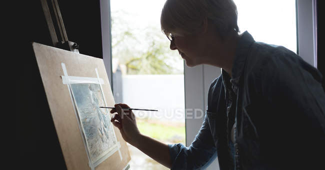 Side view of female artist painting picture on canvas at home — Stock Photo