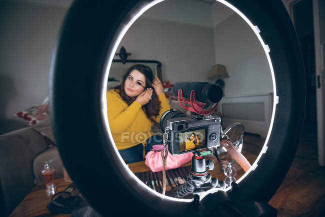 Beautiful female vlogger applying mascara at home — Stock Photo