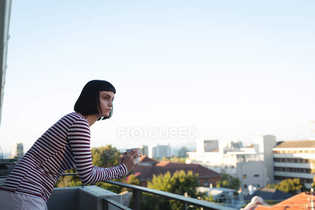 Woman having coffee in the balcony at home — Stock Photo