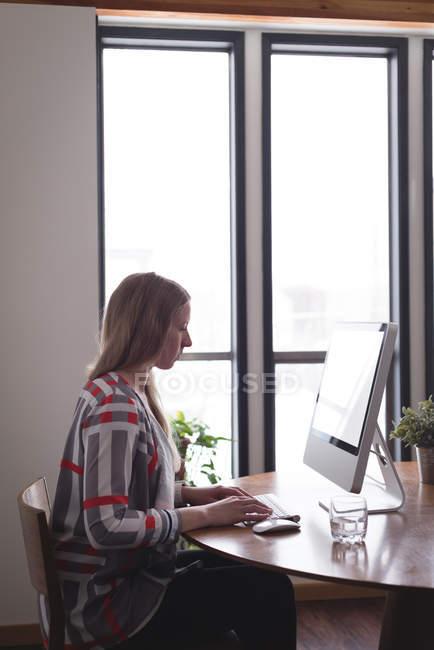 Femme cadre travaillant sur ordinateur au bureau — Photo de stock