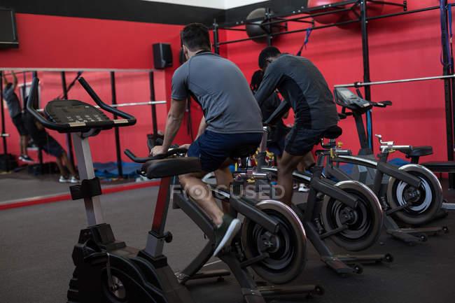Вид сзади спортсменов, занимающихся на велотренажерах в тренажерном зале — стоковое фото