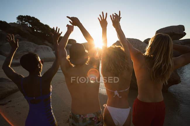 Группа друзей развлекается на пляже в сумерках — стоковое фото