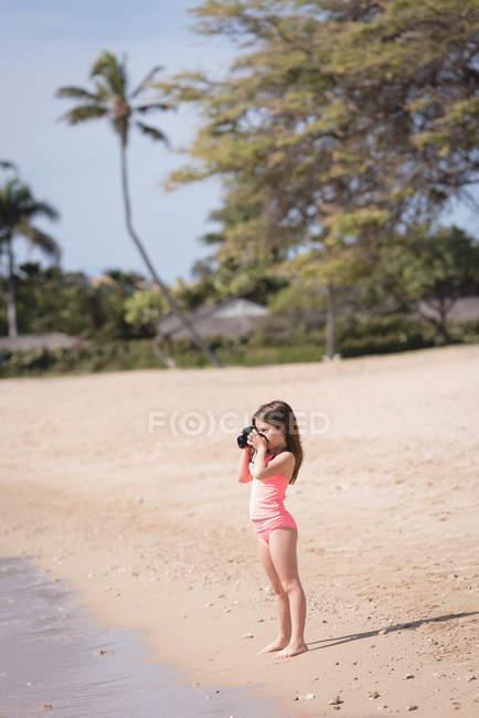 Девушка щелкает фото моря с камерой на пляже — стоковое фото