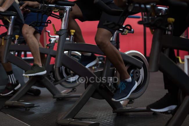 Низкая секция спортсменов, занимающихся на велотренажерах в тренажерном зале — стоковое фото