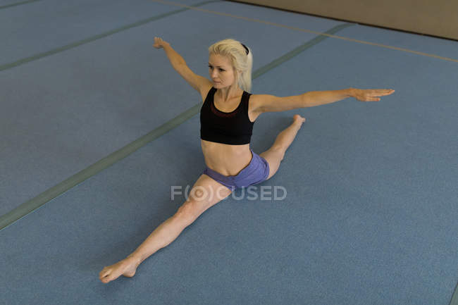 Sportswoman performing stretching exercise at fitness studio — Stock Photo