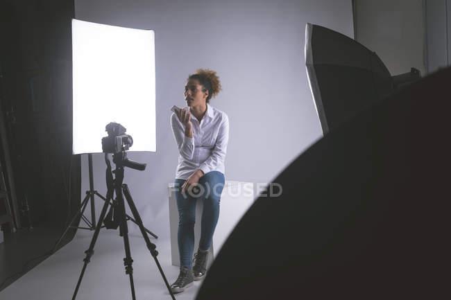 Женщина-фотограф разговаривает по мобильному телефону в фотостудии — стоковое фото