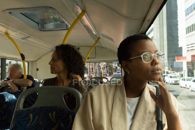 Thoughtful woman looking through window while travelling in the bus — Stock Photo