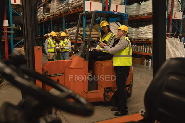 Staff discussing over digital tablet in warehouse — Stock Photo