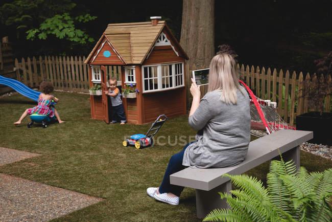 Мати фотографують грають діти в саду — стокове фото