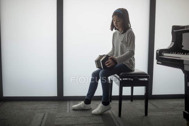 Adorable écolière jouant de l'accordéon à l'école de musique — Photo de stock