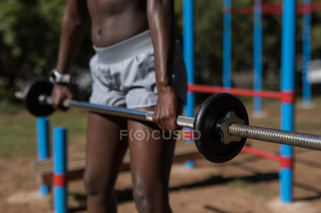 Mid section of female athlete lifting barbell — Stock Photo