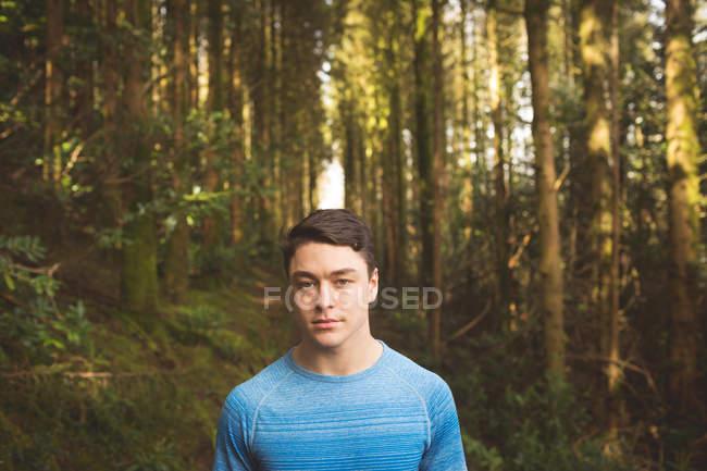 Молодой человек стоит в лесу в солнечный день — стоковое фото