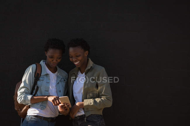 Щасливі близнюки брати і сестри використання мобільного телефону у міській вулиці — стокове фото