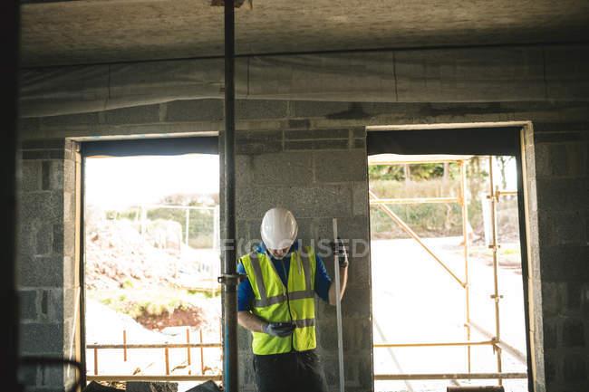 Инженер с уровнем колеи, используя свой телефон на строительной площадке — стоковое фото