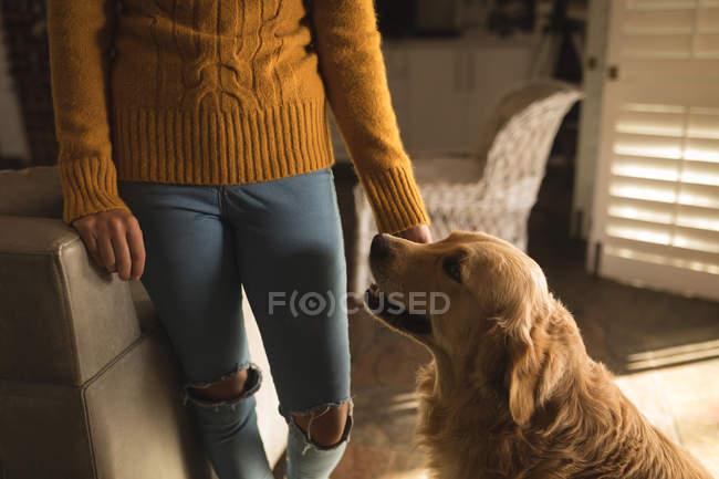 Mädchen steht mit ihrem Hund zu Hause — Stockfoto