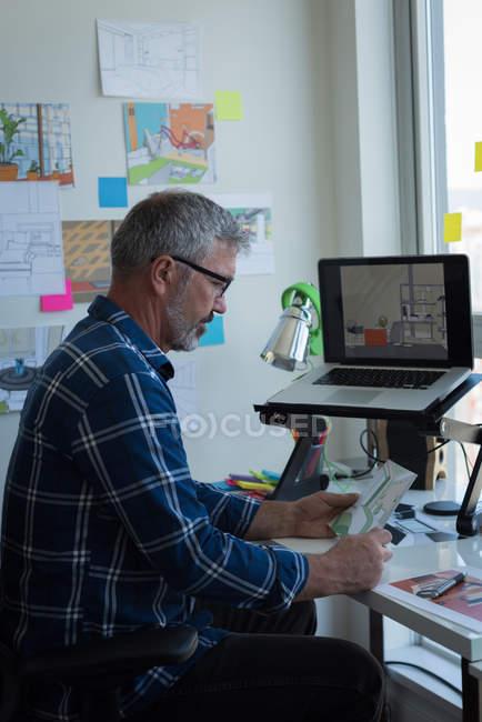 Mature man looking at architectural chart — Stock Photo