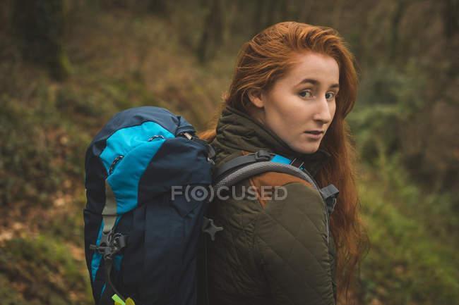 Ritratto di bella escursionista donna con zaino che guarda nella macchina fotografica — Foto stock