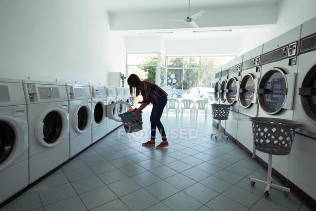 Young woman using washing machine at laundromat — Stock Photo
