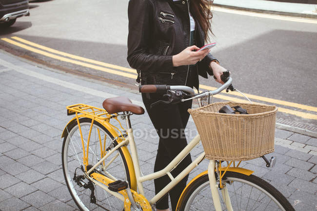 Low section of woman holding bicycle while using mobile phone on sidewalk — Stock Photo
