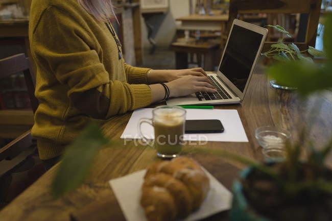 Jeune femme utilisant un ordinateur portable au café — Photo de stock