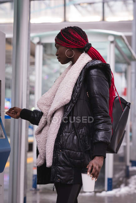 Молода жінка, використовуючи автомат квиток на вокзалі — стокове фото
