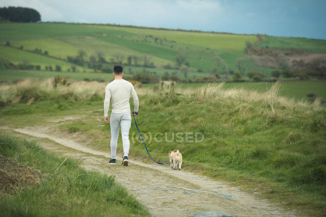 Rear view of man with his dog walking at countryside — Stock Photo