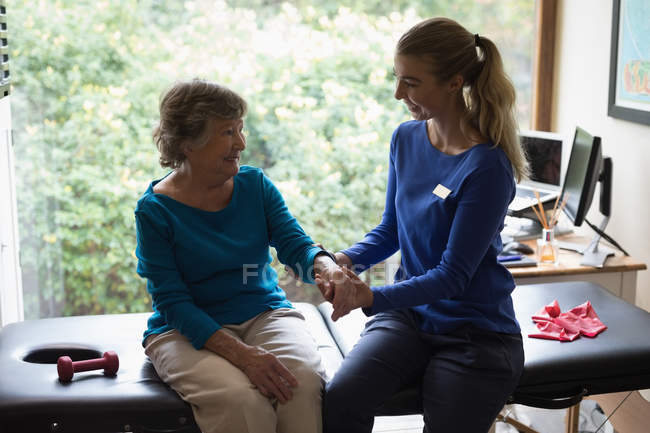 Physiotherapist giving a hand massage to a smiling senior woman — Stock Photo