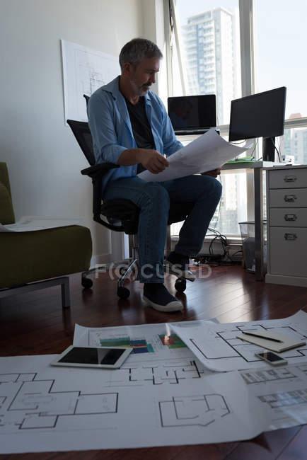 Homme mûr regardant la carte architecturale — Photo de stock