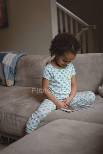 Girl sitting on the sofa and using digital tablet at home — Stock Photo