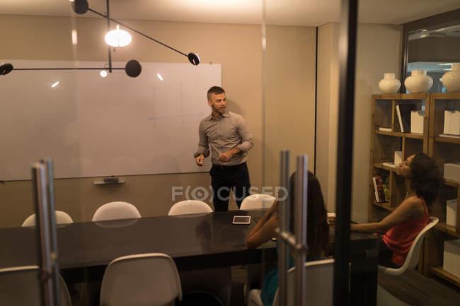 Dirigeants d'entreprises discuter au tableau blanc au bureau — Photo de stock