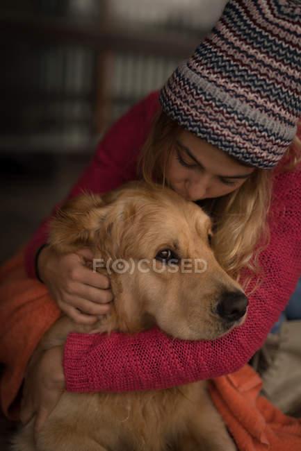 Mädchen küsst den Hund zu Hause — Stockfoto