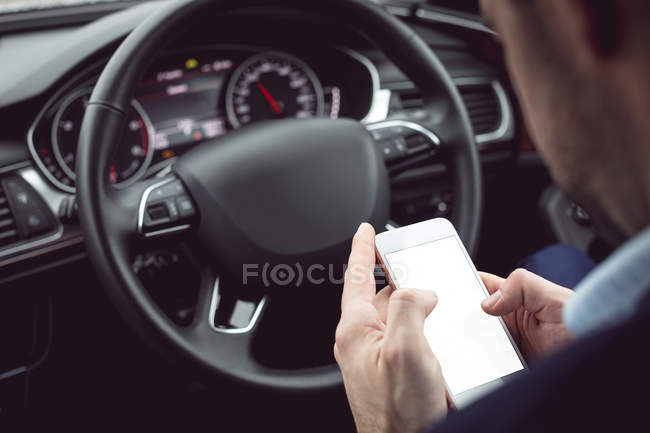 Close-up of businessman using mobile phone in a car — Stock Photo