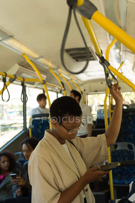 Mulher usando telefone celular enquanto viaja no ônibus — Fotografia de Stock