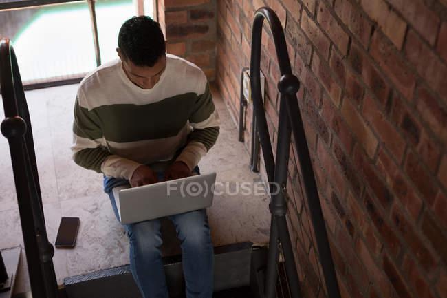 Atento hombre con laptop en escalera en casa - foto de stock