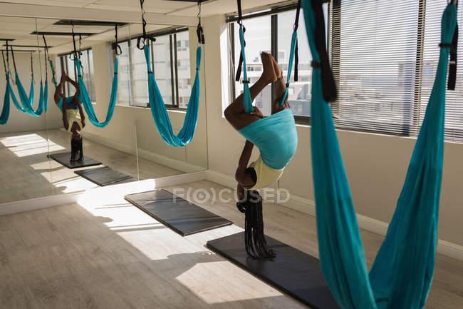 Woman exercising on swing sling hammock at fitness studio — Stock Photo