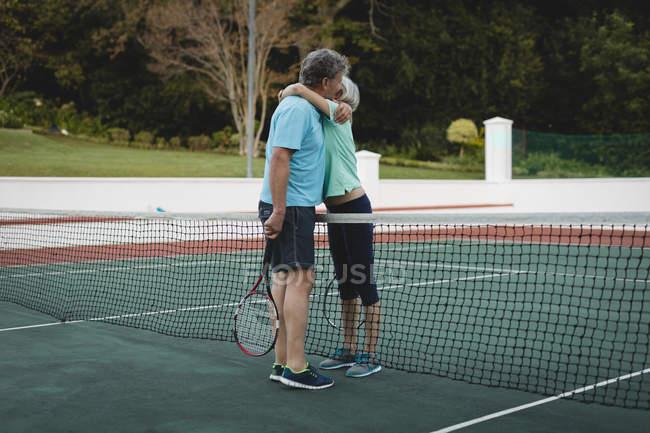 Casal sênior abraçando na quadra de tênis — Fotografia de Stock