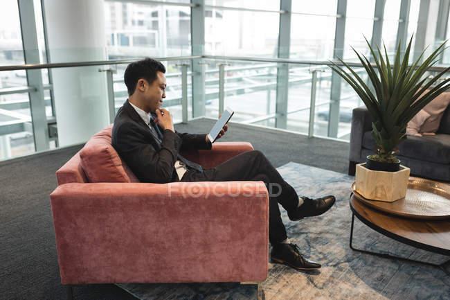 Вид сбоку бизнесмена, сидя на стуле и с помощью планшета — стоковое фото