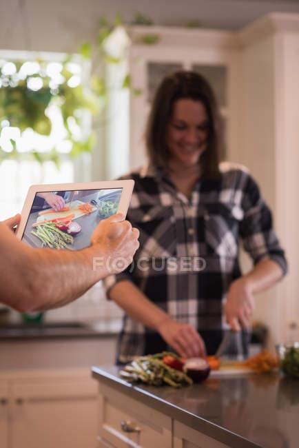 Mujer fotografía de la persona durante la cocción de alimentos en cocina - foto de stock